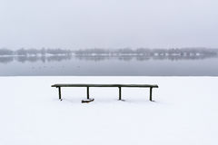 Wooden bench on the snow-covered coast of the lake. Royalty Free Stock Image