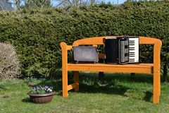Wooden bench in the spring. A wooden bench with an old satchel and accordion in the spring Stock Image