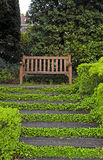 Wooden bench and staircase in garden royalty free stock images