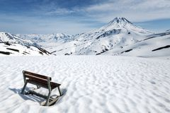 Wooden bench standing in snow for observation of volcano Royalty Free Stock Photo