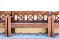 Wooden bench stands behind the house near the wall royalty free stock photo
