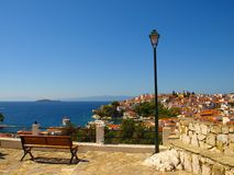 Wooden bench and street lamp with panoramic view over The Aegean Sea and Skiathos, Greece Royalty Free Stock Photos