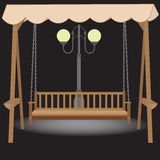 Wooden bench swing with a roof made of cloth suspended on chains Stock Images