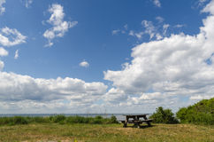 Wooden bench and table by the coast. Wooden bench and table among green vegetation by the coast Royalty Free Stock Photo