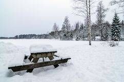 Wooden bench and table covered of snow in a snowy forest landscape panorama stock image