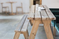 Wooden bench and table indoor. Rural rustic interior. Product display. Empty country cafe or dining room interior. Copyspace.  royalty free stock photography