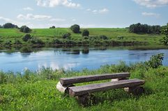 Wooden bench and table  on  the river coast Royalty Free Stock Image