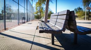 Wooden bench at the Tennis Courts. Perspective view of a wooden bench with a fence and tennis courts to the right side stock photos