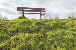 Wooden bench on the top of a Dutch dike in backlit. The slope of the deck is covered with grass and on top of the dike is an empty wooden bench. It is a cloudy Royalty Free Stock Photo