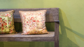 Wooden bench with two handmade pillows Royalty Free Stock Images