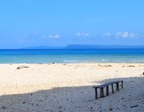 A Wooden Bench under Shade on Peaceful Secluded Sandy Beach, Blue Ocean and Sky - Laxmanpur, Neil Island, Andaman, India. This is a photograph of a wooden bench royalty free stock photos