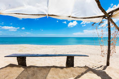 Wooden bench under a shed on the beach. A bench in the sand under a shed on a sunny beach Royalty Free Stock Image