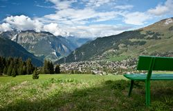Wooden bench with verbier. Green wooden bench looking on verbier town, swiss Stock Photo