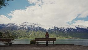 Wooden bench with view mountain landscape and blue lake. Cute girl in warm patterned coat comes to the bench and sits on. It. Mountain rear view the girl sits stock video