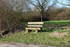 Wooden bench is waiting for an hiker. Next to an trail Royalty Free Stock Photography