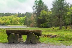 A wooden bench on the walk around Bass Lake. stock images