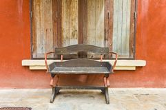 Wooden bench beside the wall. The wooden bench beside the wall and wooden windows Royalty Free Stock Image