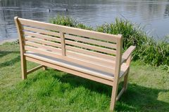 Wooden Bench on waterside Stock Images