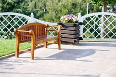 Wooden bench , white fence and flowers. A wooden bench , white fence and flowers Royalty Free Stock Photos