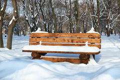 Wooden bench in the winter park. Bright sunny day and snow. Royalty Free Stock Photos