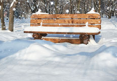 Wooden bench in the winter park. Bright sunny day and snow. Royalty Free Stock Image