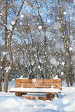 Wooden bench in the winter park. Bright sunny day and snow. Royalty Free Stock Images