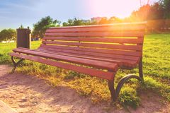 Wooden bench with wrought-iron legs and metal black trash can in. The park on a background of green lawn and sunset Stock Image