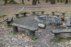 Wooden benches around fireplace in spring forest near Marianka Royalty Free Stock Photos