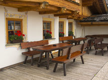 Wooden benches and beautiful windows in small alpine country house Royalty Free Stock Photo
