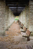 Wooden benches line in the park dried leaves. Wooden benches line in the park with dried leaves on the floor Royalty Free Stock Photos