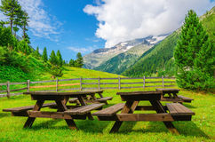 Wooden benches for picnic in Alpine valley, Alps Royalty Free Stock Photos