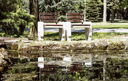 Wooden benches reflecting in water in the city park Stock Photography