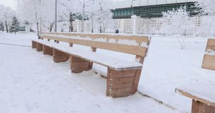 Wooden benches in the snow. In the city`s winter park snow-covered wooden benches stock footage