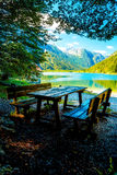 Wooden benches and a table with astonishing view on lake. Stock Images