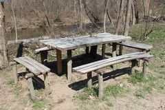 Wooden benches and table. Photo of table and four benches made out of wood, naked trees and river in background stock image