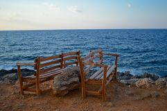 Wooden benches in the top of the rocks, with the blue sea in the background in Crete, Greece. 2 wooden bench for people, who want to rest a bit and enjoy the Royalty Free Stock Photography