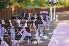 Wooden benches in the wedding ceremony area in the garden, decorated with purple ribbons. Horizontal Stock Photos