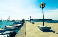 Wooden berth with street-lamp on sea background. Royalty Free Stock Image