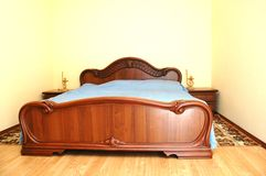 Wooden big bed in bedroom. With night table and lamp Royalty Free Stock Photography