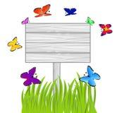 Wooden billboard, green grass and butterflies Stock Photos