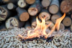 Wooden biomass - alternative energy. Renewable energy - wood and wooden pellets in flames royalty free stock image