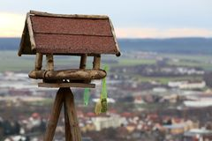 Wooden bird feeder on city background Royalty Free Stock Image
