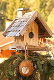 Wooden bird feeder with a coconut shell suet treats hanging Royalty Free Stock Photos