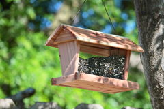 Wooden Bird Feeder Filled With Seeds Royalty Free Stock Image
