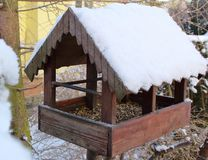 A wooden bird feeder stands on a branch nearby yellow house. A wooden feeder roof is full od snow and some bird seed is inside. stock image