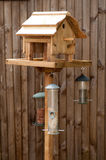 Wooden Bird Feeding Table. Bird Feeding Table with nuts and seeds hanging from it against a wooden fence Royalty Free Stock Photography