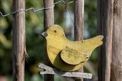 Wooden bird. In front of a picket fence stock photos
