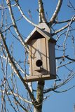 Wooden bird house. On blue sky Royalty Free Stock Images