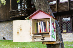 Wooden Bird house with books -reading outdoor. Decorative Bird house on a tree full of books royalty free stock photos