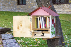 Wooden Bird house with books -reading outdoor. Decorative Bird house on a tree full of books royalty free stock image
